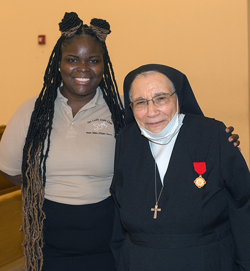 """Salesian Sister Yamile Saieh poses for a photo with Jessica Cola, 28, one of Sister Yamile's students when she taught religious education to teenagers at Notre Dame d'Haiti in Miami. Cola is now the lead singer with the Notre Dame d'Haiti youth choir and sang """"Draw Me Close To You"""" during the farewell Mass for Sister Yamile, celebrated Sept. 15, 2020, at Notre Dame."""