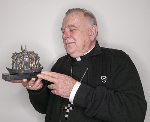 Archbishop Thomas Wenski holds a miniature replica of the Angels Unawares sculpture by Canadian artist Timothy Schmalz. A full-size replica of the immigration-themed artwork will be on display in Miami beginning Feb. 9, 2021.
