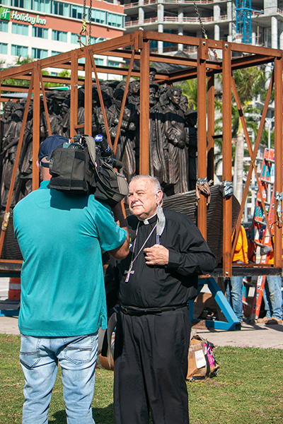 "Archbishop Thomas Wenski gives interviews to local media as workers from Florida Lemark unload and install the sculpture ""Angels Unawares"" in Miami's Bayfront Park, where it will be on display through April 8, 2021. The installation took place Feb. 9, 2021."
