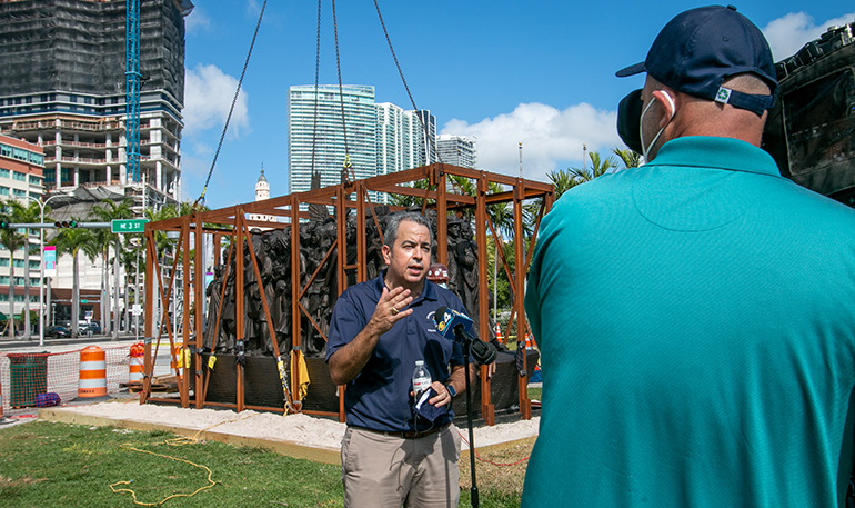 "David Prada, archdiocesan director of the Building and Property Office, gives interviews to the media as workers from Florida Lemark finish installing the sculpture ""Angels Unawares"" in Miami's Bayfront Park, where it will be on display through April 8, 2021. The installation took place Feb. 9, 2021."