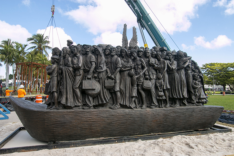 """Workers from Florida Lemark unload and install the sculpture, """"Angels Unawares"""" in Miami's Bayfront Park, where it will be on display through April 8, 2021. The installation took place Feb. 9, 2021."""