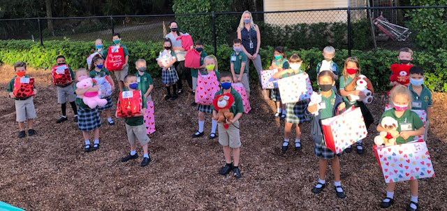 First grade students at Mary Help of Christians School pose with their teachers, Alice Smith and Janet Cefali, while holding the goody bags they filled with items for Kids in Distress of Broward, which were delivered just before Valentine's Day 2021.