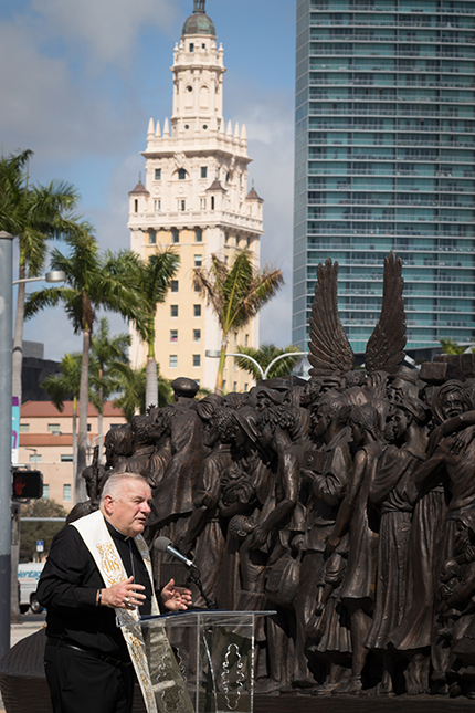 """With the Freedom Tower in the background and the sculpture behind him, Archbishop Thomas Wenski speaks at the dedication ceremony for Angels Unawares at Bayfront Park, Feb. 10, 2021. He described Miami as the """"Ellis Island of the South."""" The sculpture, a tribute to migrants and refugees, will remain at the park through April 8, 2021."""