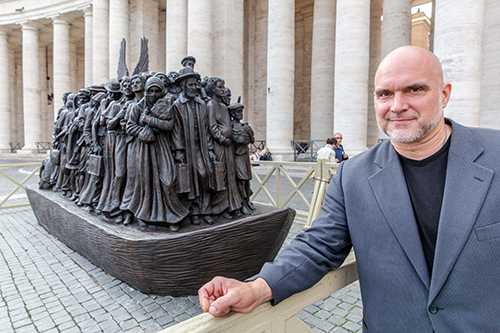 Canadian sculptor Timothy P. Schmalz poses next to his sculpture on the theme of refugees and migration titled 'Angels Unawares' in St. Peter's Square, Oct. 1, 2019.
