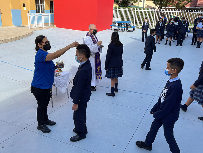 Father Juan Hernandez, pastor, and Altagracia Batista, preK aide, distribute ashes to students at Mother of Our Redeemer School, Feb. 17, 2021.