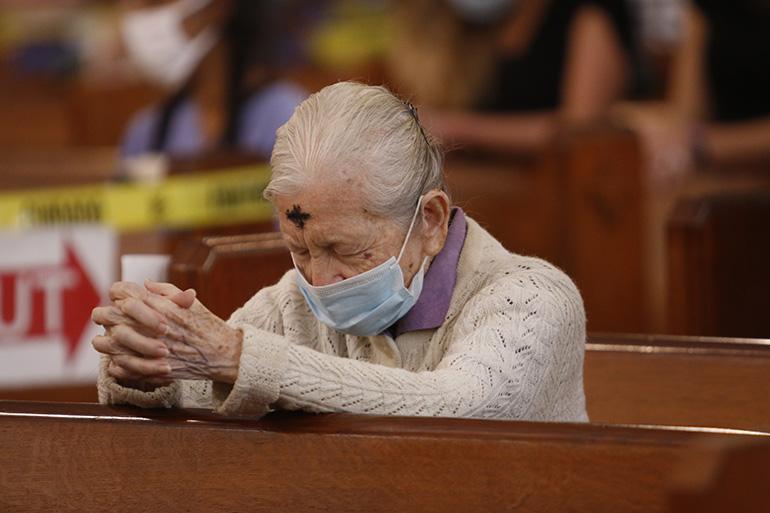 A woman prays during the Ash Wednesday Mass celebrated by Archbishop Thomas Wenski at Miami's historic Gesu Church, Feb. 17, 2021.