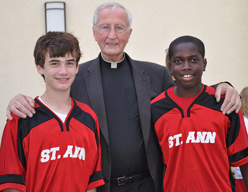 Father Seamus Murtagh is pictured in this file photo visiting with Andrew Floering, left, and Max-Oliver Ducoste-Amedee, students at St. Ann School in West Palm Beach.
