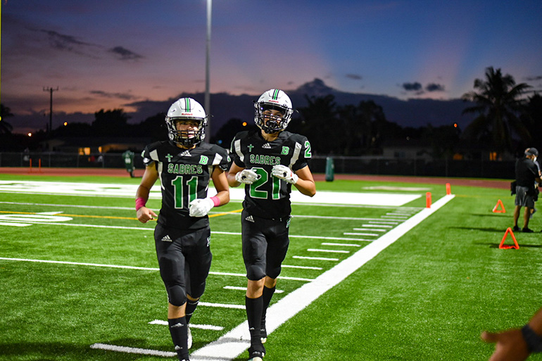 St. Brendan High wide receivers/defensive backs Jorge Cascudo (11) and Gabriel Granados (21) get off the field during an Oct. 23, 2020 game against Somerset Academy South Homestead, which St. Brendan won 48-7.