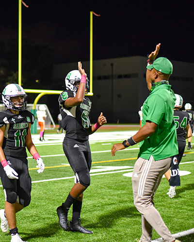 St. Brendan High wide receiver Jorge Cascudo (11) and quarterback Damari Charlton are congratulated by coach during a game they won 48-7 against Somerset Academy South Homestead, Oct, 23, 2020.