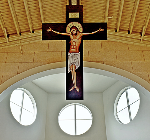 Above the chancel, a full-size crucifixion icon hangs at an angle, making it visible even to those sitting in the front.