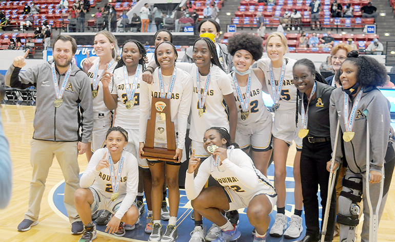 St. Thomas Aquinas players and coaches celebrate with the championship trophy after their 62-60 victory over Wekiva in the FHSAA Class 6A girls basketball championship game Saturday, Feb. 27, 2021, at the RP Funding Center in Lakeland. The Raiders won their first championship.
