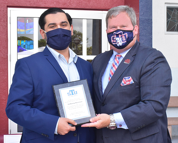 Anthony Barroso, left, gets a plaque from President David Armstrong of St. Thomas University for his action against an anti-Semitic graffito. The presentation took place March 2, 2021.
