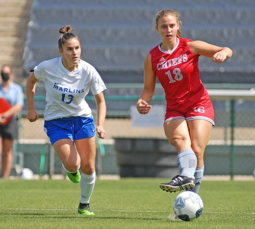 Cardinal Gibbons junior Sydney Polivka, right, passes away from Arnold's Olivia Lebdaoui during the first half of Cardinal Gibbons' 2-0 victory over Panama City Beach Arnold in the FHSAA Class 4A girls soccer championship game March 3, 2021, at Spec Martin Stadium in DeLand. Polivka scored a goal, and the Chiefs won their first girls soccer championship.