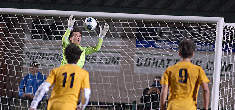 Belen Jesuit backup goalkeeper Jack Volpe leaps to make a save in front of teammates Alejandro Pereyra (11) and Matias Perinot (9) during the second overtime of the Belen Jesuit Wolverines' 2-1 overtime victory over the Tampa Jesuit Tigers, March 6, 2021 in the FHSAA Class 5A Boys Soccer Championship Game at Spec Martin Stadium in DeLand. Belen Jesuit denied seven-time champ Tampa Jesuit a repeat Class 5A title, and the Wolverines won their second state title and first since 2016.