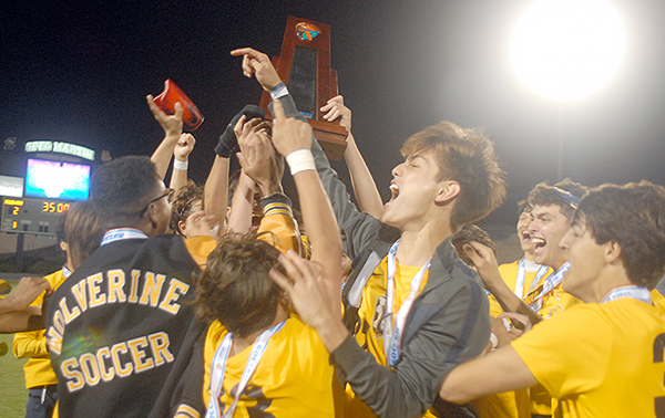 Belen Jesuit players celebrate with the championship trophy after the Wolverines' 2-1 overtime victory over the Tampa Jesuit Tigers, March 6, 2021 in the FHSAA Class 5A Boys Soccer Championship Game at Spec Martin Stadium in DeLand.