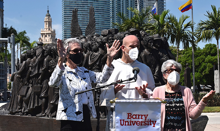 """Leaders of Barry University lead a Dominican prayer in Miami during the announcement of the university's new Institute for Immigration Studies. From left are Sister Mary Anne Caulfield, regional superior of the Adrian Dominican Sisters; Father Cristobal Torres, campus chaplain at Barry; and Sister Linda Bevilacqua, past president of the university. Behind them is the sculpture """"Angels Unawares,"""" on display at Bayfront Park."""