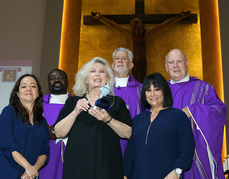 Jackson Memorial Hospital representatives stand with priests after the Mass where they were honored by Corpus Christi Parish, Feb. 28, 2021. From left: Madeline Barrios, community outreach manager at Jackson Health System; Father Joseph Jean-Louis, parochial vicar at Sacred Heart Parish in Homestead; Mariana Martinez, chairperson of the International Kids Foundation Wonderfund, holding the plaque; Father Jose Luis Menendez, Corpus Christi pastor; Maylen Montoto, associate director of Event and Sponsorship Sales at the Jackson Health Foundation; and Father Federico Capdepon, a retired archdiocesan priest who helps at Corpus Christi.