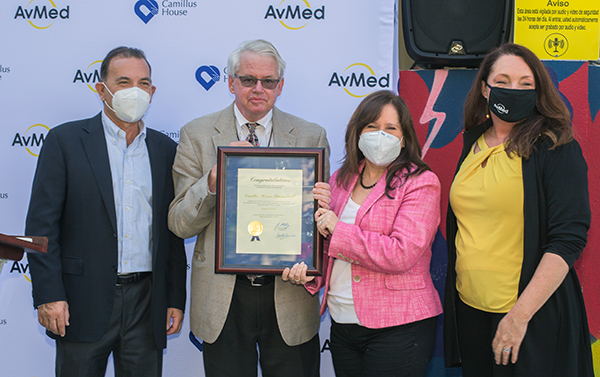 Posing with the proclamation from Miami-Dade County Mayor Daniella Levine Cava, from left: Paul Lowenthal, Camillus House chairman of the board, Patrick Morris, director of Civic and Philanthropic Partnerships for the mayor's office, Hilda Fernandez, Camillus House CEO, and Ashley Allen, senior vice president of Strategic Growth and Marketing for AvMed, whose donation of outdoor fitness equipment to Camillus House's main campus inspired the Fit 'n Trim celebration March 24, 2021.