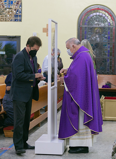 Archbishop Thomas Wenski distributes Communion Peter Routsis-Arroyo, CEO of Catholic Charities, during the agency's 90th anniversary Mass at St. Joachim Church in Miami, March 26, 2021. A temporary barrier helps maintain social distance during the COVID-19 pandemic.