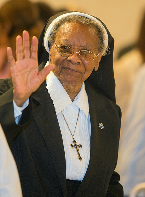 Sister Clementina Givens waves at other religious the Mass marking her diamond jubilee (75th anniversary) of religious life, celebrated at St. Patrick Church, Miami Beach, Sept. 12, 2015.