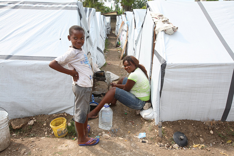 Child earthquake refugees pose for the camera at a tent city in Port-au-Prince in the file photo from March 2010. One decade later, tens of thousands are still living in tent camps.