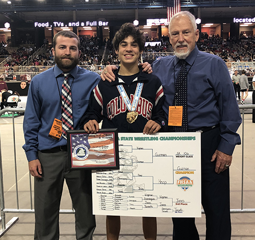 Columbus state wrestling champion Christian Guzman is pictured here with wrestling coaches Jacob Grant, left, and head varsity wrestling coach Jim Husk, right.