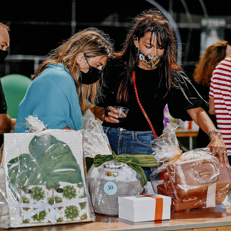 """Participants look over the baskets they will """"bid"""" on during Immaculata-La Salle High School's Tricky Tray fundraising event March 18, 2021. Funds will go toward a new athletic field and fine arts building at the Miami high school."""