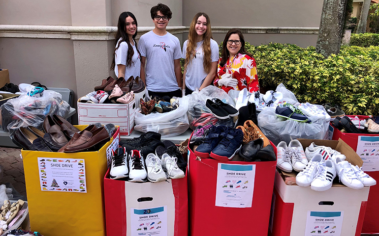 The Inguanzo siblings, Susanna, Sophia and Christopher, pose with Camillus House CEO Hilda Fernandez while sorting, cleaning and packing the 5,000 pairs of donated shoes, March 20, 2021.