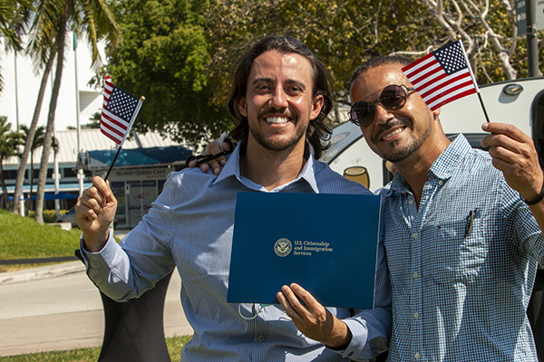"New U.S. citizen Michael Pimenta, left, poses with his naturalization certificate, American flag, and friend Andre Rosa after the ceremony held in the shadow of the ""Angels Unawares"" sculpture and Miami's Freedom Tower, March 24, 2021."