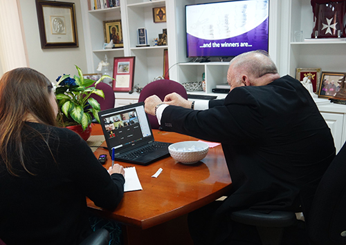 """Archbishop Thomas Wenski shows parish representatives on a Zoom call the name of a winner in the """"stretch goal"""" raffle as Katie Blanco Bourdeau, cabinet secretary of Stewardship and Development for the archdiocese, takes notes."""