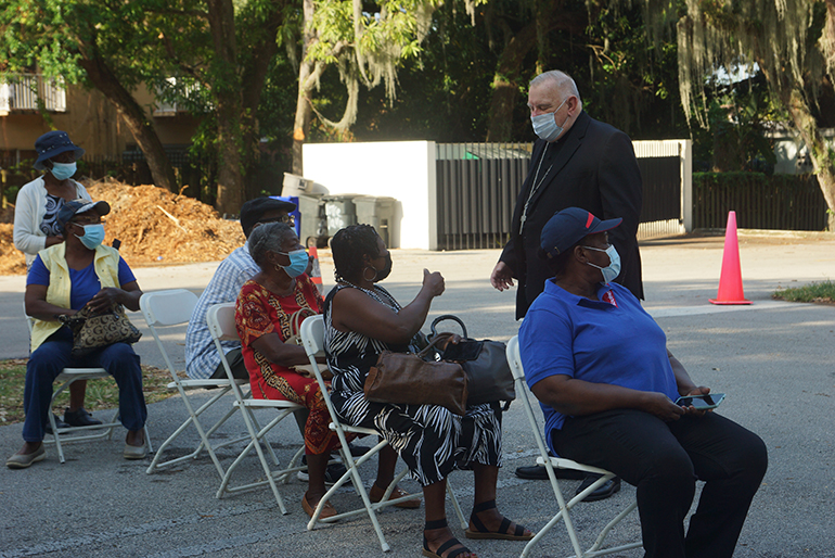 Archbishop Thomas Wenski speaks to people waiting to get vaccinated against COVID-19 at Notre Dame d'Haiti Mission in Miami on April 14, 2021. He recently put out a video in Creole urging the Haitian community to get vaccinated.