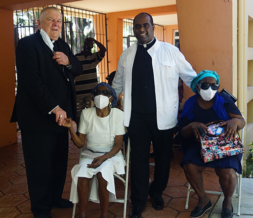 Archbishop Thomas Wenski poses with Father Reginald Jean-Mary, administrator of Notre Dame d'Haiti Mission in Miami, which hosted a vaccination event April 14, 2021. With them are Father Jean-Mary's 92-year old mother and his sister, who also waited their turn to receive the vaccine.