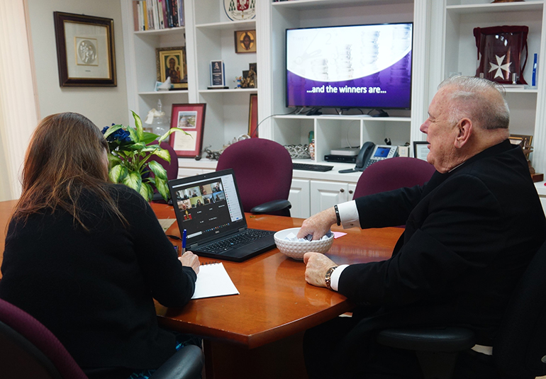 """Katie Blanco Bourdeau, cabinet secretary of Stewardship and Development for the archdiocese, takes notes as Archbishop Thomas Wenski picks the winners of the """"stretch goal"""" raffle from among the parishes that collected more than their """"stretch goal"""" in the 2020 ABCD campaign."""