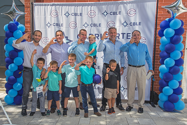 """Throwing up the """"C"""" for Christopher Columbus High School, from left: Brian Carricarte, Andrew Carricarte, Louie Carricarte, Michael Carricarte, Jr., Michael Carricarte, Sr. and their male children, future Columbus students. The Carricarte family gave their name and support to Columbus' business career pathway, now named the Carricarte Business, Leadership and Entrepreneurship program, at a ceremony held April 15, 2021 at the all-boys Miami high school."""
