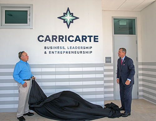 Michael Carricarte, Sr., and Juan Vila, academic dean at Christopher Columbus High School, unveil the Carricarte Business, Leadership and Entrepreneurship logo outside the business classroom April 15, 2021. The family of alums gave its name and support to the business career pathway at the all-boys Miami high school.