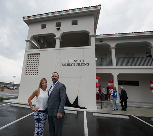 Shaun Smith-Myers, Cardinal Gibbons class of '89, and Charlie Myers pose in front of the Phil Smith Family Building after the name was unveiled, April 21, 2021.