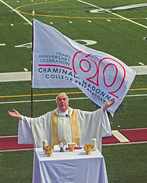 Marianist Father Robert Bouffier, school chaplain, celebrates the Mass marking Chaminade-Madonna College Preparatory's 60th anniversary, April 25, 2021 at the school's Vince Zappone Field.