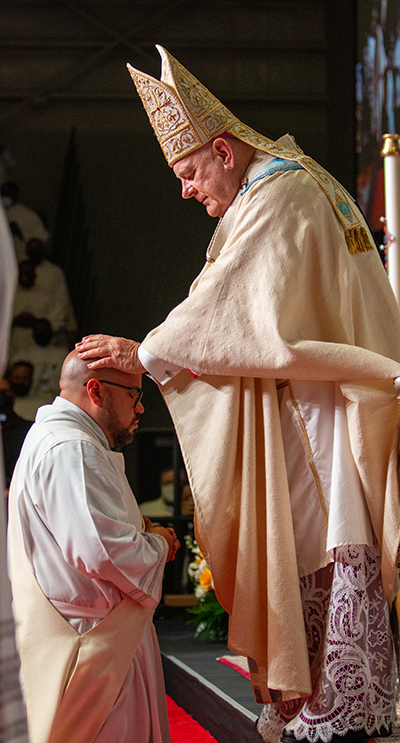 Archbishop Thomas Wenski lays hands on Deacon Alberto Chavez, ordaining him as one of eight new priests for the Archdiocese of Miami, May 8, 2021.
