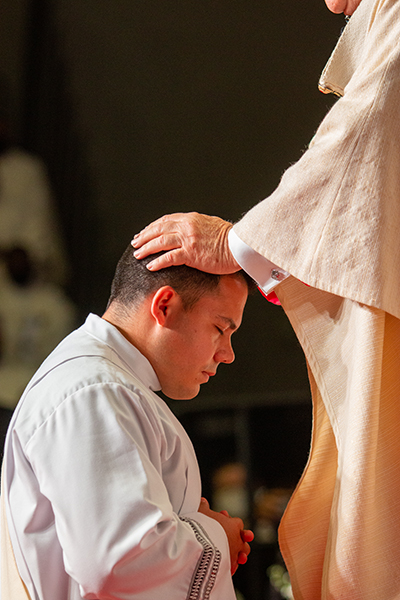 Archbishop Thomas Wenski lays hands on Deacon Nicholas Toledo, ordaining him as one of eight new priests for the Archdiocese of Miami, May 8, 2021.
