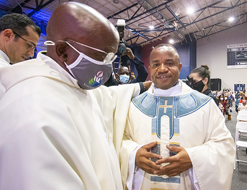 Newly ordained Father Franklin Ekezie wears his priestly vestments after being vested by a fellow Nigerian who welcomed him into his parish, Father Samuel Muodiaju, left, pastor of St. Monica in Miami Gardens.
