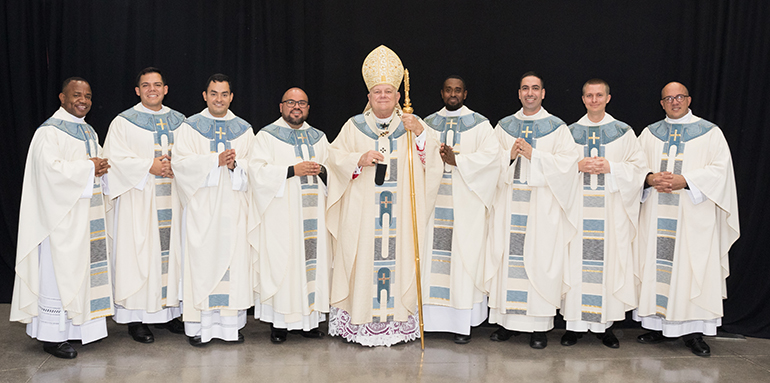Newly ordained priests take the official photo. From left: Father Franklin Ekezie, Father Nicholas Toledo, Father Hans Chamorro, Father Alberto Chavez, Archbishop Thomas Wenski, Father Jeremy Lully, Father Leandro Siqueira, Father Paul Pierce, and Father Yosbany Alfonso.