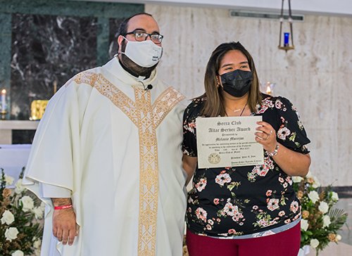 Melanie Morejon, 18, who has served weekly at Immaculate Conception Church in Hialeah even through the COVID pandemic, receives her altar server award from Father Matthew Gomez, chaplain of the Miami Serra Club and archdiocesan vocations director. The awards Mass was celebrated May 15, 2021 at St. John Vianney College Seminary in Miami.