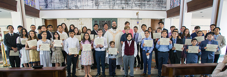 Father Matthew Gomez and the 46 altar servers who received Serra Club awards for their dedication pose for a photo in St. Raphael Chapel on the campus of St. John Vianney College Seminary. Father Gomez, Serra Club chaplain and archdiocesan vocations director, celebrated the Mass May 15, 2021.