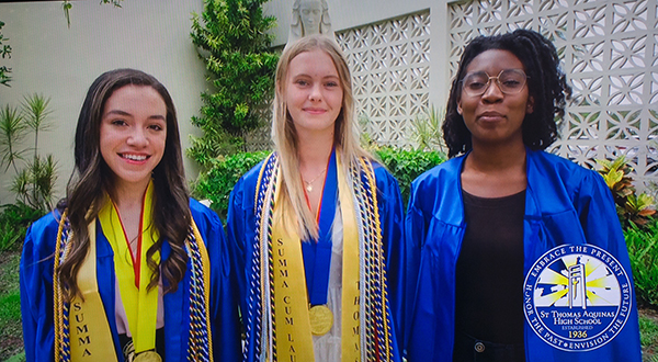Offering greetings from their school in a loop that ran before the start of the baccalaureate Mass, from left: St. Thomas Aquinas High School's Kamila Trigueros, salutatorian, Victoria Szymkiewicz, valedictorian, and Archbishop's Leadership Award winner Kensia Saint-Hilaire. Representatives of nine of the 12 Catholic high schools in the Archdiocese of Miami took part in the Mass, celebrated by Archbishop Thomas Wenski May 24, 2021 at St. Mary Cathedral.
