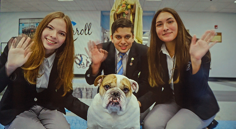 Offering greetings from their school in a loop that ran before the start of the baccalaureate Mass, from left: Archbishop Coleman Carroll High's Elizabeth Fitzgerald, 18, valedictorian; Daniel Valdez, 19, Archbishop's Leadership Award winner; Camila Gloria, 18, salutatorian, and the school's bulldog mascot, Archie. Representatives of nine of the 12 Catholic high schools in the Archdiocese of Miami took part in the Mass, celebrated by Archbishop Thomas Wenski May 24, 2021 at St. Mary Cathedral.