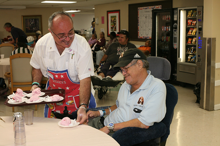 In this file photo from 2014, Vinnie Pisciotta serves ice cream to Watercrest resident David Woodruff during a visit by the Emmaus Brothers of St. Rose of Lima Parish to the nursing home. The National Center on Elder Abuse reports that seniors are actively involved in or contacted regularly by religious congregations more than any other demographic group. In addition, clergy, and representatives from one's faith community are among the few, and in many cases, the only people who visit a senior's home or care facility.