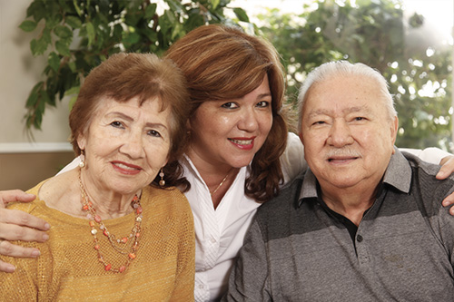 In this file photo from 2019, Jackie Pareja, Social Service Coordinator at St. Boniface Gardens, poses with her parents who are residents of the facility. Catholic Housing Management, a division of Catholic Health Services, currently operates 16 HUD subsidized apartment complexes for active, independent seniors with limited financial resources in Miami-Dade and Broward counties.