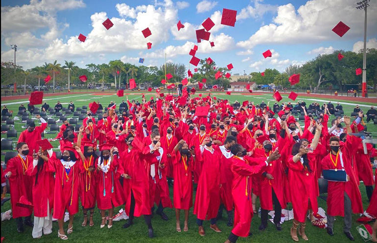 Msgr. Edward Pace High School's class of 2021 throw their caps into the air after their graduation ceremony, held May 28, 2021 on the school's new football field.