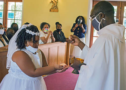 Spiritan Father Fidelis Nwankwo, administrator of St. Philip Neri Parish, gives first Holy Communion to Gabriella Williams, 9, during Mass on Trinity Sunday, May 30, 2021.