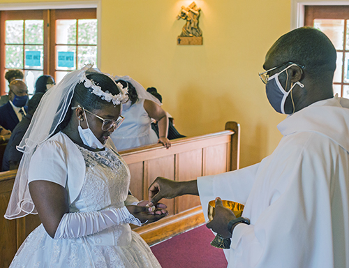 Father Fidelis Nwankwo, administrator of St. Philip Neri Parish, gives first Communion to Emari Miller, 11, during Mass on Trinity Sunday, May 30, 2021.